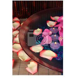 Fototapeta Płatki róż i świece w wodzie w wazonie